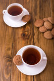 Tea and oaten cookies on a wooden table Royalty Free Stock Photos