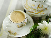 Tea for one. Single tea cup with ferns and flower in background royalty free stock photos