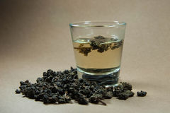 Tea with Oolong in glass on brown background. Royalty Free Stock Images