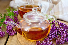 Tea of oregano in glass teapot on board with cup Royalty Free Stock Images