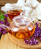 Tea from oregano in glass teapot and cup on board Royalty Free Stock Photo