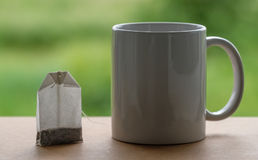 Tea package and a mug. On a background of green field Stock Photo