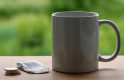 Tea package and a mug with coins. On a green background Royalty Free Stock Photography