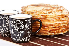 Tea and a pancakes. Cups with tea and a pile of pancakes on a plate Stock Images