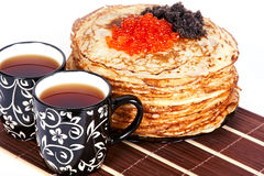 Tea and a pancakes with caviar. Cups with tea and a pile of pancakes with caviar on a plate Stock Image