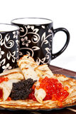 Tea and a pancakes with caviar. Cups with tea and a pile of pancakes with caviar on a plate Stock Photo