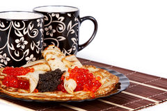 Tea and a pancakes with caviar. Cups with tea and a pile of pancakes with caviar on a plate Royalty Free Stock Images