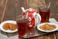 Tea pancakes. Glassful teapot tea pancakes in Russian style Royalty Free Stock Image