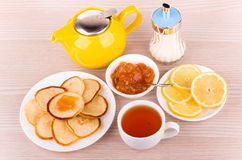 Tea with pancakes, peach jam and lemon, sugar and teapot Stock Images