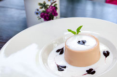 Tea panna cotta dessert. Dessert with blueberries sirup, mint leaf and cream Royalty Free Stock Images