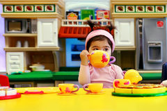 Tea party. A fifteen months old baby girl having a tea party with her baby dolls Stock Photography