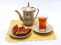 Tea party with baklava. Still life with teakettle, saucer and baklava on a yellow cloth royalty free stock images