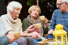 Tea Party with Best Friends. Elderly people wearing warm clothes enjoying each others company while having tea party with delicious cake outdoors royalty free stock photography