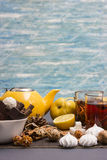Tea party on a blue background. Yellow teapot, two glass cups of tea, sweets, candy, cinnamon, nuts, lemon and pear Royalty Free Stock Photography