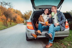Tea party in car trunk - loving couple drinks hot tea from thermos flask sitting in car trunk Royalty Free Stock Photography