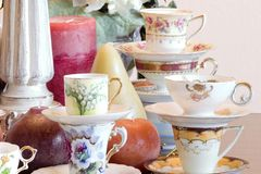 Tea Party closeup. Vintage tea cups, tea pot, candles and flowers, just add finger sandwiches or chocolate truffles for an afternoon tea party or just use as a Stock Photo