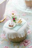Tea party cupcake. Cupcake decorated with a tiny fondant tea set royalty free stock photography