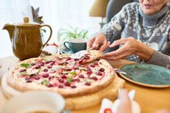 Tea Party at Full Speed. Close-up shot of unrecognizable elderly women putting slice of appetizing dessert pizza on her plate while having tea party at home stock image