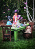 Tea Party in the Garden. Six year old girl playing tea party with her three year old brother in the garden Royalty Free Stock Photos