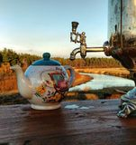 The tea party on the nature near the river. Still life kettle on the backgroundof nature and the river Stock Photo