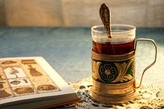Tea Party. Open book. Glass-holder on the table.Glass of tea Royalty Free Stock Photo
