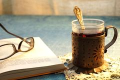 Tea Party. Open book. Glass-holder on the table.Glass of tea Stock Photos