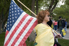 Tea Party Patriot Carrying US Flag, Denver. DENVER, COLORADO – APRIL 15: A women displays her American flag at the Tea Party Patriots Rally in Downtown Denver Royalty Free Stock Photos