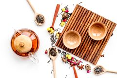 Tea party set. Tea pot, cups, dried tea leaves, fllowers, spices on white background top view Stock Photography
