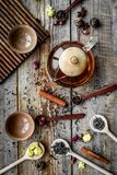 Tea party set. Tea pot, cups, dried tea leaves, fllowers, spices on wooden background top view Stock Image