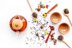 Tea party set. Tea pot, cups, dried tea leaves, fllowers, spices on white background top view.  Stock Images