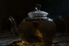Tea Party. Transparent glass teapot is on the table. Inside teapot flower blossoms - welding Stock Images