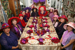 Tea party women. Twelve fashionable women sitting down for a tea party Royalty Free Stock Photos
