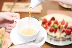 Tea party. Women pour green tea into a white Cup stock photo