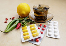 Tea, peppers,lemon natural remedies vs pills Royalty Free Stock Image