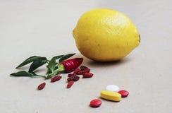 Tea, peppers,lemon natural remedies vs pills Royalty Free Stock Images