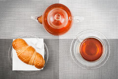 Tea. Photo of a cup of tea, teapot and croissant. The top view royalty free stock photos