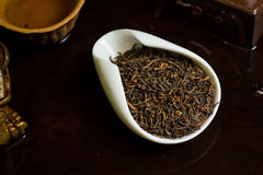 Tea in cup dry on table served. Chinese tea pile in a cup closeup Stock Photo