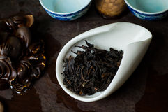 Chinese tea leaves served on table. Chinese tea pile in a cup closeup Stock Photos