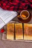 Tea, plaid, cake and a book. Stock Image