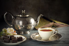 Tea in a porcelain cup, old fashioned silver teapot, chocolate c Royalty Free Stock Photo