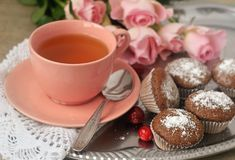 Tea in a porcelain pink cup, chocolate muffins, pink roses. Close-up Royalty Free Stock Images