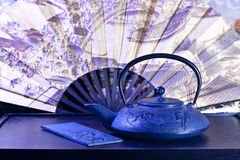 Tea pot. Cast iron tea pot and plate with japanese fan stock image