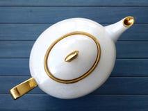 Tea Pot. An old white tea pot on a blue wooden table Stock Photography