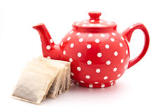 Tea pot. Red colourful teapot isolated on white with teabags for context Royalty Free Stock Photos