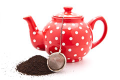 Tea pot. Red colourful teapot isolated on white with tea leaves and strainer for context Royalty Free Stock Photos