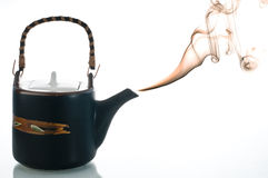 Tea pot. Smoking teapot with different colored smoked on back background Stock Photos