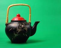 Tea pot. Asian style tea pot served on a green background Stock Photo