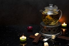 Tea pot, candles, shockolate, waffles, dark background stock photo