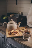 Tea pot and cookies in rustic grey kitchen interior. Slow living in country house concept Stock Photos