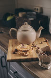 Tea pot and cookies in rustic grey kitchen interior. Slow living in country house concept Royalty Free Stock Image